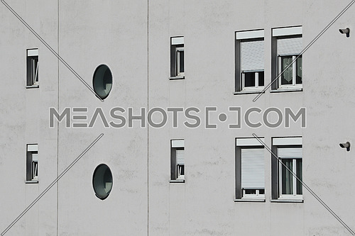 Different window shapes on light gray cement facade background