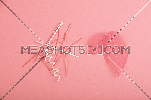 Pink skeleton leaves and paper cuts, stripes and spirals over design paper background