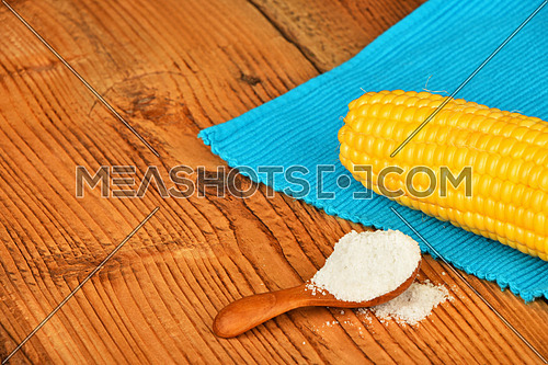 One open fresh yellow corn cob and salt in scoop with blue cloth napkin on brown vintage wooden surface