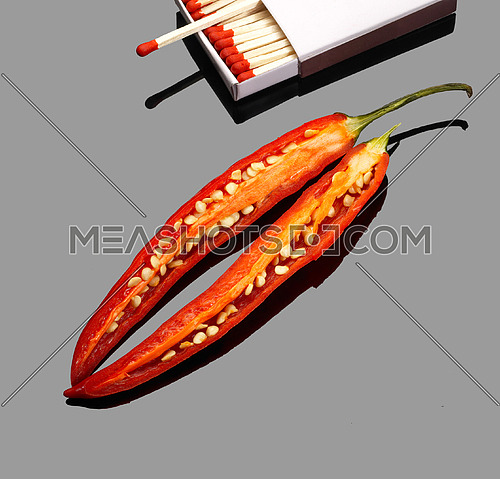 fresh red chili peppers  with matches over grey reflective surface