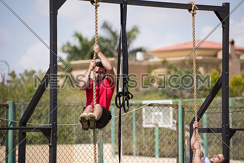 young middle eastern athletic man strenuous exercise climbing the rope outside on a sunny day