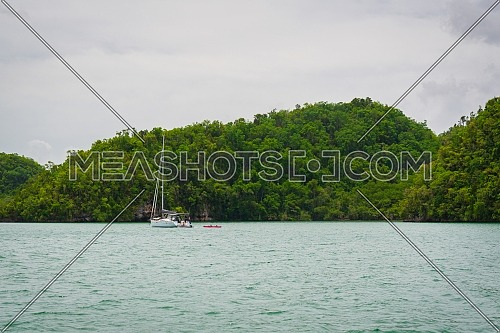 Luxury boat anchored close to exotic tropical island. Panoramic landscape view of Los Haitises natural park,Samana peninsula in Dominican republic.