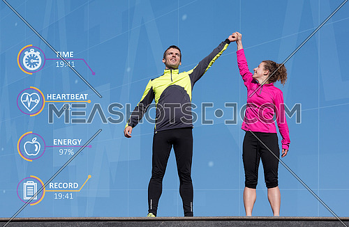 Happy fitness runner couple with arms raised up in winning gesture expression