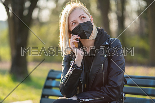 Woman using a Smart phone in the park sitting on a bench in a park on a sunny day, wearing black medical mask for protection, during Coronavirus quarantine.
