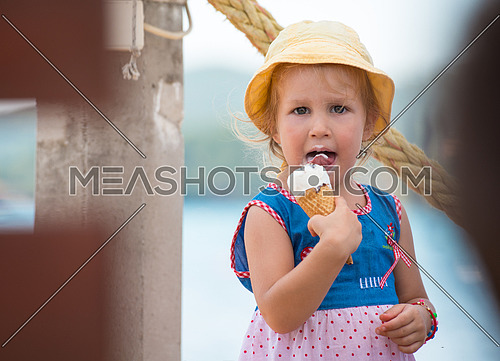 adorable little girl eating ice cream on beach by the sea during Summer vacation