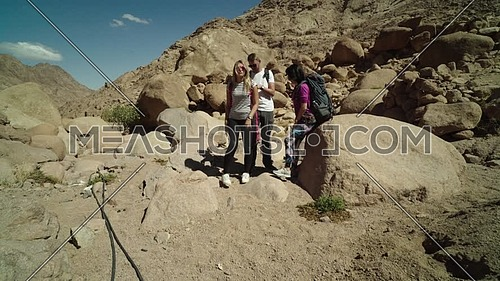 Follow shot for a group of tourists wearing backpacks standing and getting ready for exploring Sinai Mountain for wadi Freij at day.