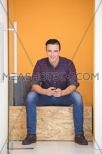 young man in crative box working on smart phone, startup business modern office room  interior