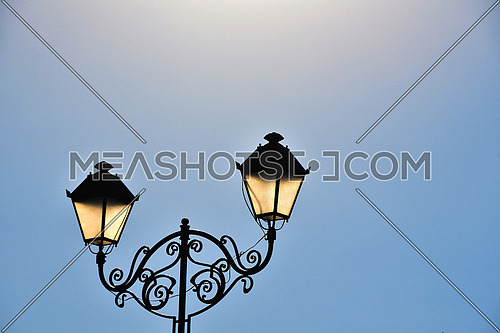 Street antique style double lamp post with effect of shine at late day blue sky background