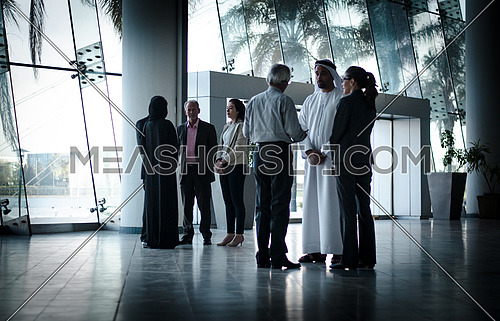 two groups in business meeting, a Khaliji Arab man included