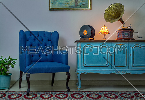 Interior shot of blue armchair, vintage wooden light blue sideboard, lighted antique table lamp, old phonograph (gramophone), vinyl records on background of beige wall and tiled porcelain floor