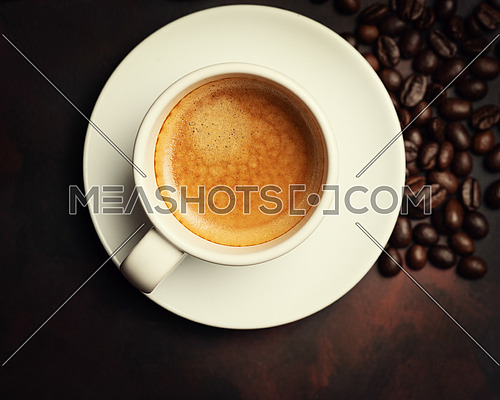 White cup of coffee and coffee bean on dark background. Copy space. Top view.