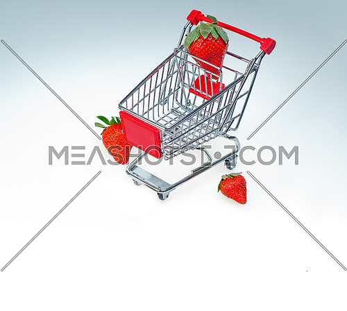 strawberry on shopping cart over white