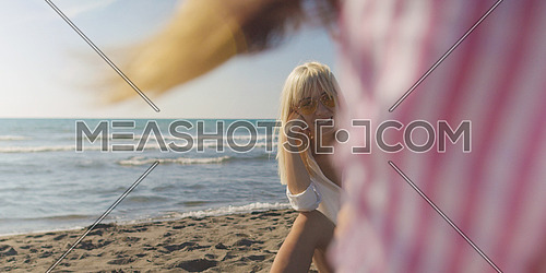Two Girl Friends Taking Photo with Smartphone On Empty Beach during autumn day