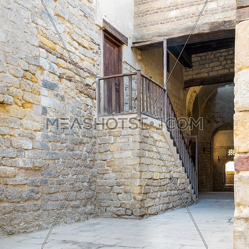 Exterior daylight shot of old abandoned staircase with wooden balustrade and wooden door at stone bricks passage surrounding Sultan Qalawun Complex located in Al Moez Street, Cairo, Egypt