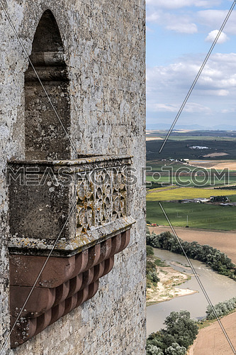 Almodovar del Rio, Cordoba, Spain - June 9, 2018: Detail of balcony in one of the towers of the castle, scenery of the river Guadalquivir, It is a fortitude of Moslem origin, Almodovar del Rio, Spain