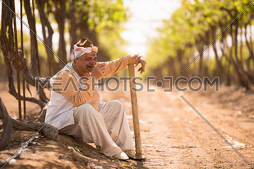 older middle eastern farmer sitting a large modern farm