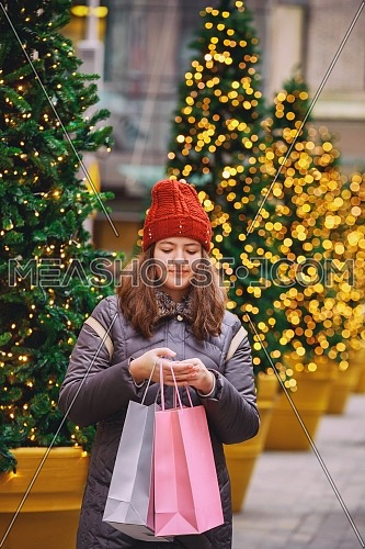 Young happy girl with shopping bags crossing a city street, colorful lights bokeh background