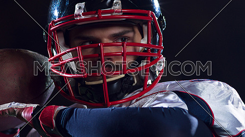 american football player throwing rugby ball against black background
