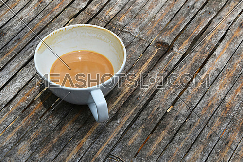 One almost overdrunk finished white cup of latte cappuccino coffee on old vintage bamboo table