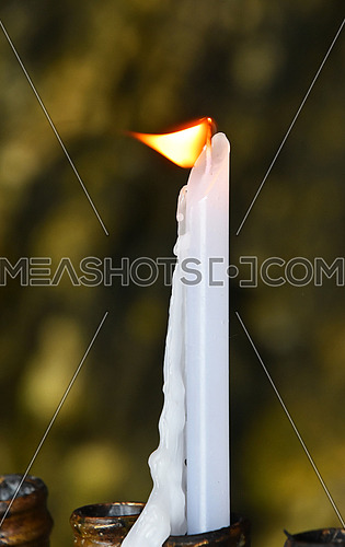 Burning white wax religious melting candle flame trembling in temple or church over vivid background