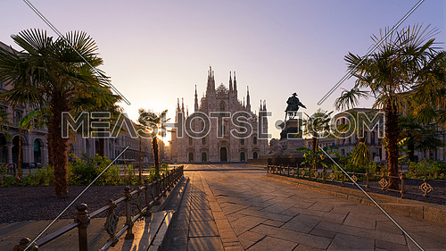 Duomo square with new exotic palms tree , Milan gothic cathedral at sunrise,Europe.