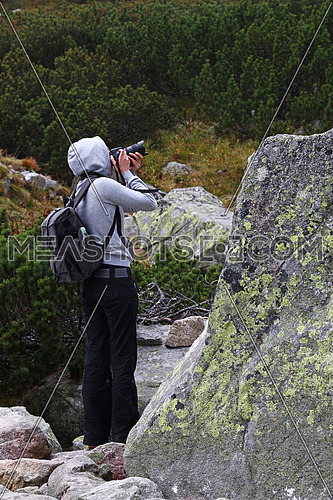 One young tourist woman with backpack wearing hoodie taking pictures in mountains on foggy weather day, low angle rear side view