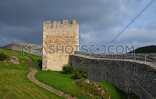 Tower and wall of Spissky hrad or Spis Castle ruins in Slovakia, one of the largest castle sites in Central Europe, built in 12th century, summer day with dramatic cloudy sky