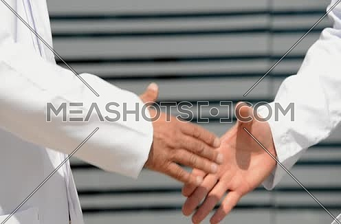 close up of doctor and patient shaking hands