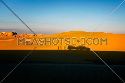 Desert Safari 4x4 white car and tourists silhouette shadow in Nature Reserve Desert Dunes landscape with blue sky , Arial View Fayoum , Egypt