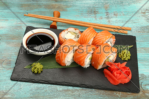 Close up set of six Philadelphia sushi rolls with raw salmon served on black slate board on blue table, high angle view