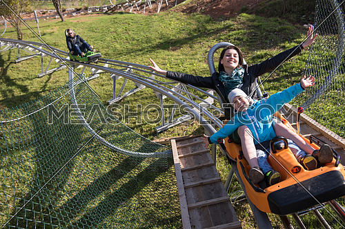 young excited mother and son enjoys driving on alpine coaster