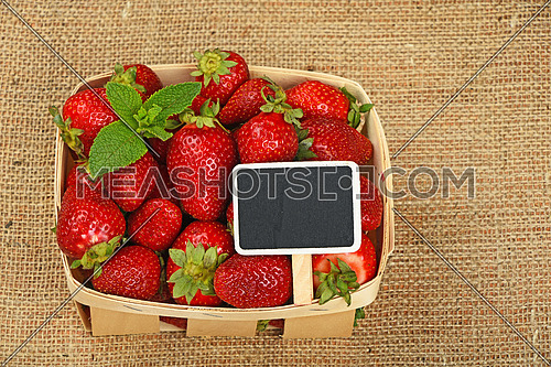 Wicker wooden basket of strawberries with mint leaves and chalk blackboard price tag sign on jute burlap canvas background, high angle view