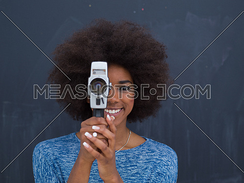 A young beautiful african american woman using a retro video camera isolated on a gray background