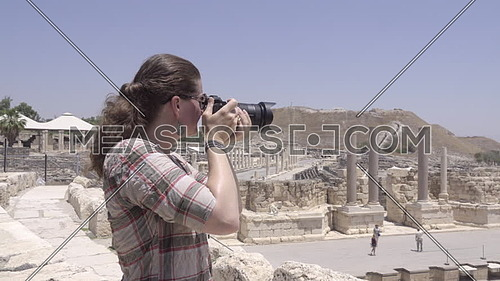Scene of female tourist photographing ampitheater ruins at Beit Shean