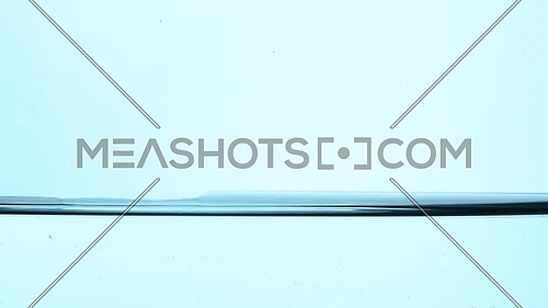 Shaking pure clear cold water surface level in transparent glass jar or teapot, close up, low angle side view, slow motion