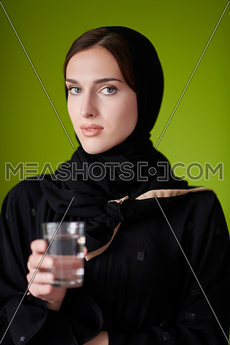 Modern muslim woman in abaya holding a glass of water in front of her. Arab girl representing iftar time, Ramadan kareem concept