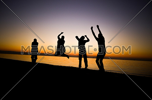 4 friends having fun and jumping at the beach, enjoying the sunset golden hour