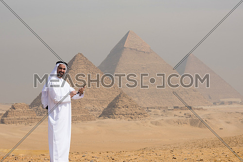 arabian business man using tablet computer in desert with great giza pyramids in background