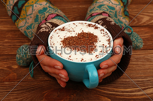 Close up two woman hands hold and hug big full cup of latte cappuccino coffee with heart shaped chocolate on milk froth over brown wooden table, high angle view