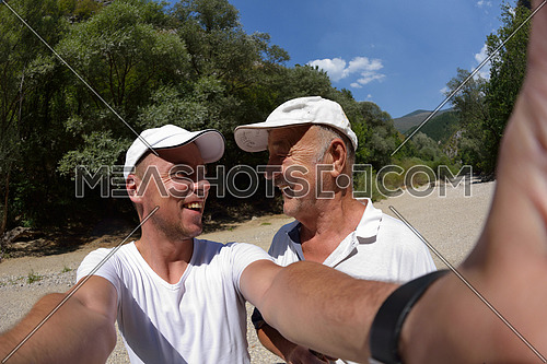 senior dad and son taking selfie photos on  hiking tour