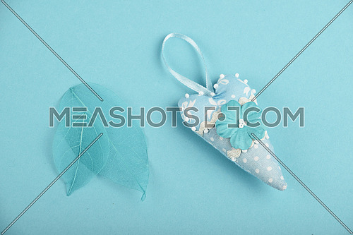 Blue small toy textile heart and two skeleton leaves over design paper background