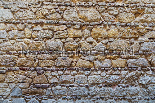 Background of pattern of yellow and gray decorative grunge weathered uneven stone wall surface