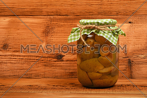 One big glass jar of homemade pear compote with green checkered textile top decoration at brown vintage wooden surface