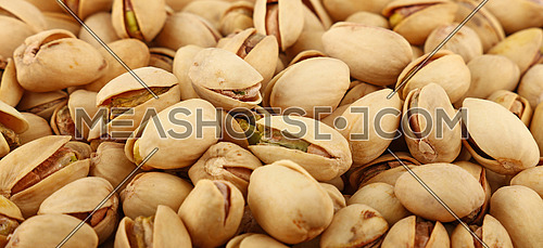 Background texture of fresh roasted pistachio nuts, elevated, high angle top view
