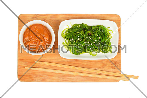 Portion of Asian green marinated seaweed salad in small white plate with peanut sauce on bamboo wooden board with chopsticks isolated on white