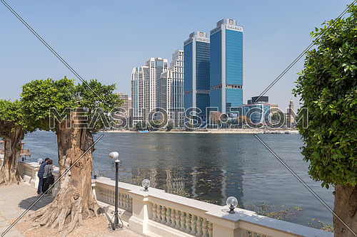 Cairo, Egypt - March 10, 2018: City view from River Nile with overlooking Head Office of National Bank of Egypt and St. Regis hotel with two people looking at the Nile