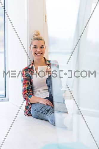Portrait of a beautiful girl who is sitting on the floor and drinking coffee