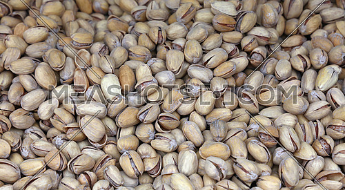 Whole salted roasted pistachio nuts with nutshells on retail market, close up, high angle view background
