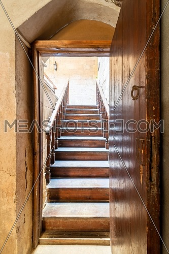 Open wooden door revealing wooden old staircase going up with with reflections of the stairs on the door located at the House of Egyptian Architecture historical building, Cairo, Egypt