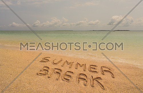 In the photo a beach in Zanzibar in the afternoon where there is an inscription on the sand (Summer Break).